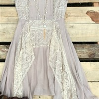 asymmetrical dress with lace detail through out with a scoop neckline. It has a layered