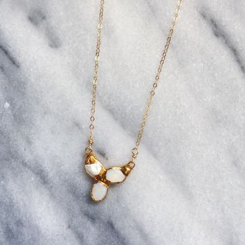 Small mother of pearl cluster necklace on a chain.