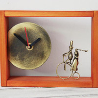 Lovers brass clock, lovers on a bike art object, orange wooden frame, rectangular clock with oxidised brass sculptures, lovers art object