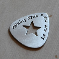 Handmade aluminum guitar pick by Nici Laskin with cut out star