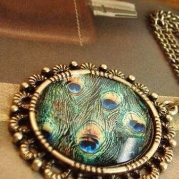 Beautiful Peacock Feathers arranged into this round Pendent that hangs on a Long Sweater Chain