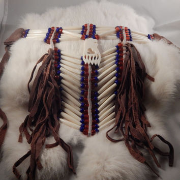 Drop bone choker with white hair pipe and glass pony beads - deerskin fringe; carved bone bear drop, red white and blue - veterans regalia