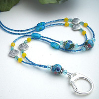 This beaded id badge lanyard features lovely round flower polymer clay beads predominately blue with some hints of yellow, pink and green. There are three of these, each capped at both ends with a pretty silver bead cap and aqua blue crystals. Silver shel