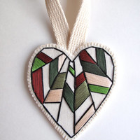Valentines Day heart ornament hand embroidered in earthy colors of greens, brown, eggshell white and burgundy on bright cream muslin