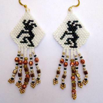 Beaded earring, kopeli pattern in black seed beads with white background and hanging various shapes of beads. Handmade