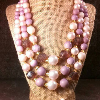 Fancy shades of purple and gold, white and ivory, pink triple strand beaded necklace and clip earrings.