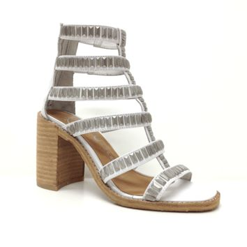 Turn heads in this trendy Potomac Gladiator Sandals by Jeffrey Campbell! Featuring open toe, t-strap gladiator construction at shaft, elasticized detail on the top two straps, silver studded accents, cut out designs, and cut-out chunky heel. Finished with