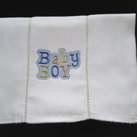 Baby Boy embroidered on a  burp cloth in blues, greens and gold the seams have decorative stitches. Can be personalized for an extra charge.