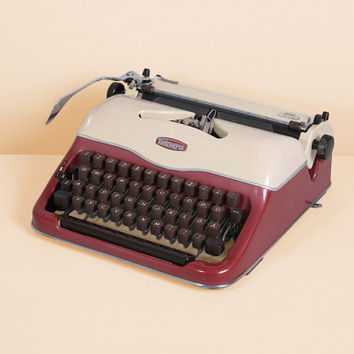 ca. 1960 Triumph Norm Typewriter. Restored and in very good working conditon. Dark pink. Portable. With Case.