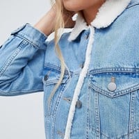 ASOS DESIGN denim jacket with fleece collar in midwash blue at asos.com