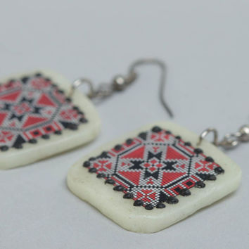 Handmade polymer clay white earrings with red and black ornament in ethnic style