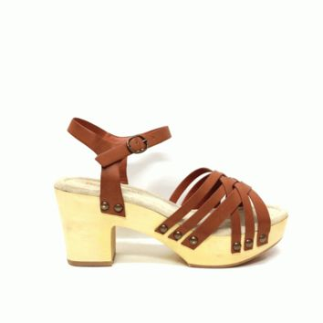 Show off in fashionable look with this Trendy Cate Strappy Wooden Platform Sandal by Restricted Footwear! Featuring a strappy construction at vamp, an adjustable ankle buckle closure for easy on/off, natural wooden platform, antique gold color studded deta