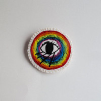 Rainbow eye brooch hand embroidered on cream muslin and a cream felt backing An Astrid Endeavor Summer trends