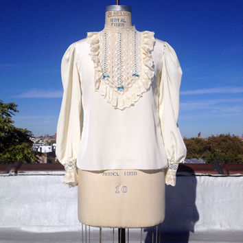 Vintage 1980's cream colored blouse with lace, ribbon, and ruffle details, size medium