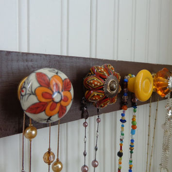 Beautiful dark brown distressed wooden wall plaque with decorative knobs for organizing jewelry.