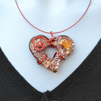 A lovely red glass heart pendent embedded with silver and copper flakes and wire wrapped with accent beads on a matched necklace.