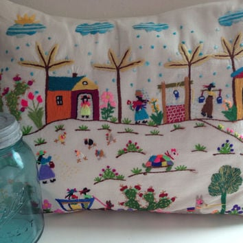 Embroidered pillow with a village scene of flowers, people, chickens, horses and clouds in like new condition