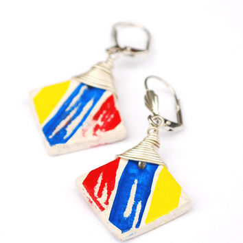A pair of very colorful earrings. Red, blue and yellow stripes on white background. Shabby street style jewelry.
