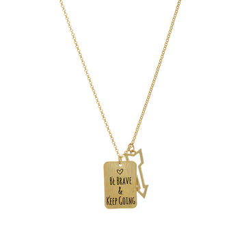 "Gold tone necklace featuring a plate stamped ""BE BRAVE & KEEP GOING"" and an open arrow charm."