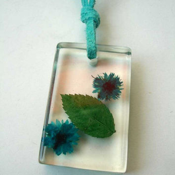 Beautiful resin pendant with real flowers in turquoise