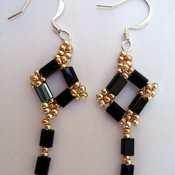 Dangling earrings with black and silver tone rectangle beads,gold and silver Miyuki seed beads  and silver tone ear wires. Handmade