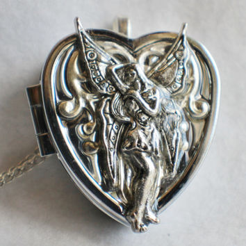 Music box locket, heart shaped locket with music box inside, in silver with fairy and filigree adornments.