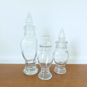 Three tall thin glass apothecary jars with pointed stoppers for display, terrariums or storage