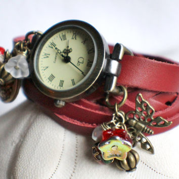 Leather strap wrist watch, in red with teardrop locket, bronze butterfly and bead charms.