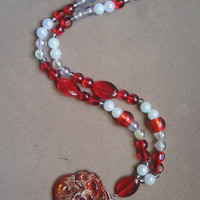 Red and white necklace with pendant.