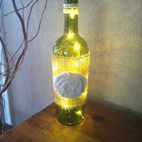 Burlap and lace decorated wine bottle with flower.