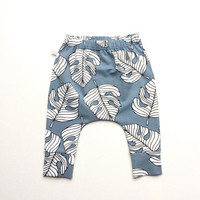 Blue slim fit harem pants with monstera leaves. Organic baby or infant pants. Jersey knit fabric. Kids leggings with cuffs. Monstera pants