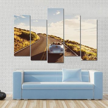 Happy Couple Driving On Country Road In Classic Vintage Sports Car Multi Panel Canvas Wall Art