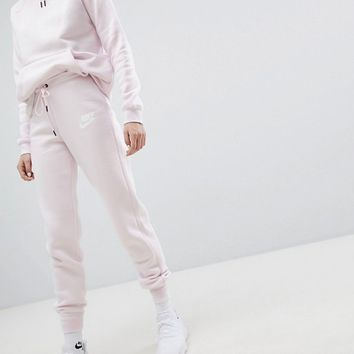 Nike Rally Tight Fit Joggers In Pearl Pink at asos.com