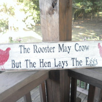 The rooster may crow but the hen lays the eggs. country sign, funny country sign, chicken sign, egg sign white sign, wood sign, humerous