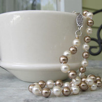 Gorgeous knotted bronze and white Swarovski crystal pearl strand with an antique silver tone clasp.