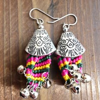 Silver earrings with bells, fabric, and silver detailed bead caps.
