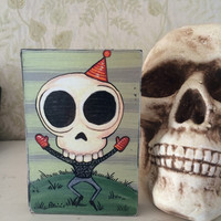 skull guy with mittens print on wood block