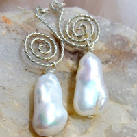 Not your ordinary pearl drop earrings, lustrous white Keshi baroque shaped pearls dangle from a silver swirl