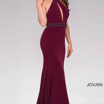 Burgundy long fitted sleeveless dress with high jeweled neckline and a key hole opening.