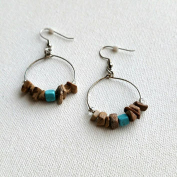 Circular beaded tan and turquoise earrings.