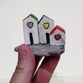Ceramic sculpture , ceramic miniature of three little ceramic houses with tiny hearts , on a Granite stone with sparkly Quartz crystals