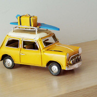Yellow Mini Cooper replica, retro collectible metal car replica with surfboard and suitcase on baggage rack