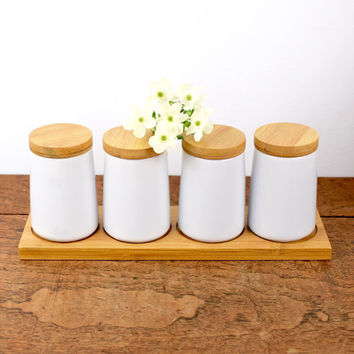Set of four vintage white ceramic spice storage jars with wooden lids