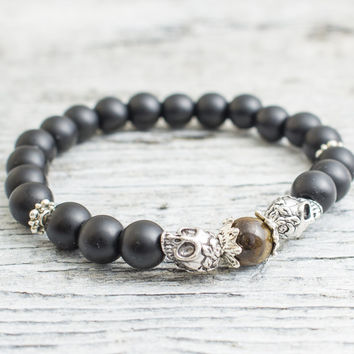 Matte black lava stone beaded double silver skull and a tiger eye bead, stretchy bracelet, yoga bracelet, mens bracelet, womens bracelet