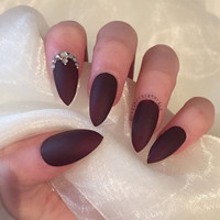 Burgundy matte stiletto nails with rhinestone and gold bead details