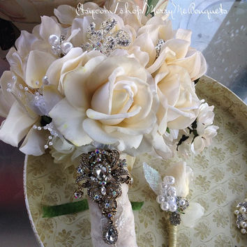 Ivory rose brooch bouquet with matching boutonniere. Wedding bouquet