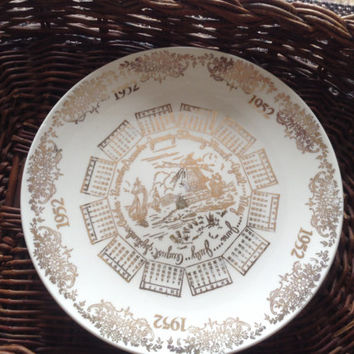 Commemorative 1952 plate with kitchy charm, gold on ivory background