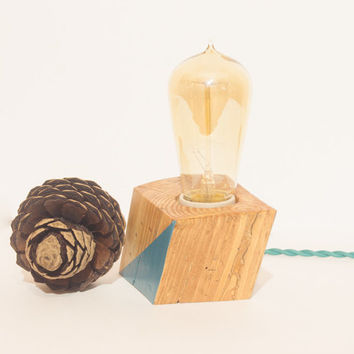 Small wood lamp made out of reclaimed pine wood with modern blue geometric accent on sides.
