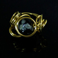 Gold tone wire ring molded around a Snowflake Obsidian stone