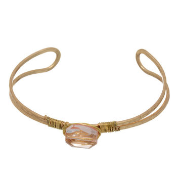 Worn gold tone cuff bracelet featuring a rose pink wire wrapped glass stone.